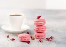 Roze makarons met droge bloemknoppen en kop van koffie pastelkleur royalty-vrije stock foto