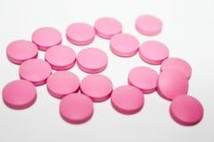 Roze medische pillen op witte achtergrond stock afbeeldingen