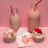 Roze milkshakeflessen en cupcakes Stock Foto's