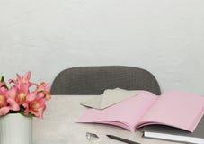 Roze nota's, boek, envelop, bloemen over grijs bureau stock foto