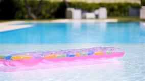 Roze opblaasbare matras die op waterspiegel in zwembad drijven stock video