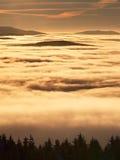 Roze oranje zonstijging boven nevelige de winterbergen stock afbeelding