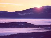 Roze oranje zonstijging boven nevelige de winterbergen Royalty-vrije Stock Foto's