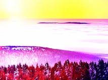 Roze oranje zonstijging boven nevelige de winterbergen, shinning mist Pieken van bergen Stock Afbeelding