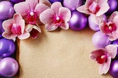 Roze orchideebloemen en violette Kerstmisballen rond uitstekende sh Royalty-vrije Stock Foto's