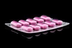Roze Pillen op Zwarte Stock Foto's