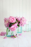 Roze pioenen in glaskruiken stock fotografie