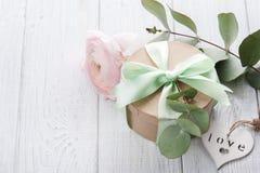 Roze ranunculus en giftdoos met groen lint Stock Fotografie