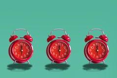 Roze Retro Wekker drie, op een pastelkleur blauwe achtergrond royalty-vrije stock afbeelding