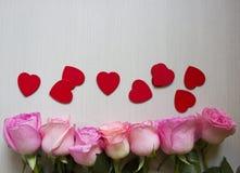 Roze rozen en harten over houten lijst De achtergrond van de valentijnskaartendag stock afbeeldingen