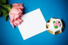 Roze rozen, kaart en cake met roze marsepeinrozen op blauwe achtergrond Royalty-vrije Stock Fotografie