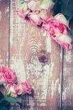 Roze rozen op oude houten raad Stock Afbeeldingen