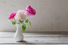 Roze rozen in vaas op witte achtergrond stock afbeelding