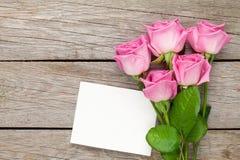 Roze rozenboeket en lege groetkaart over houten lijst Stock Afbeeldingen
