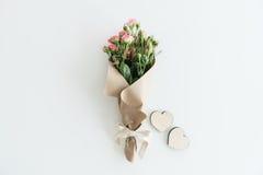 Roze rozenboeket in kraftpapier-document met twee houten die harten op wit met exemplaarruimte worden geïsoleerd Stock Foto's