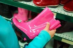Roze rubberlaarzen in de kind` s handen van de koper royalty-vrije stock fotografie