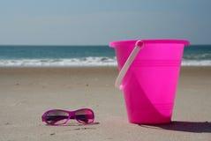 Roze schaduwen en emmer op het strand Stock Afbeeldingen