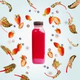 Roze smoothiefles met vliegende bessen en snijbietenbladeren op lichtblauwe achtergrond Gezonde detoxdranken royalty-vrije stock afbeeldingen