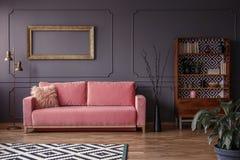 Roze sofa tegen grijze muur met model van gouden kader in elega royalty-vrije stock foto