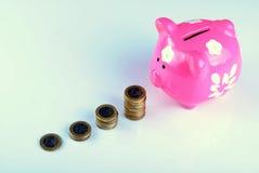 Roze spaarvarken met euro muntstukken, zachte schaduwen Stock Foto's