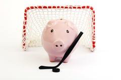 Roze spaarvarken met zwarte hockeystok en zwarte hockeypuck en rode hockeypoort met witte netto op witte achtergrond Royalty-vrije Stock Foto's