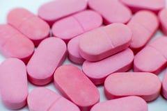 Roze stapel van tablettenvitaminen of pillen stock afbeelding
