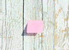 Roze sticker op oude houten achtergrond Textuur van witte geschilderde raad Royalty-vrije Stock Afbeeldingen