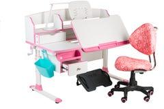 Roze stoel, roze schoolbank, blauwe mand, bureaulamp en zwarte steun onder benen Stock Foto