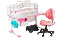 Roze stoel, roze schoolbank, blauwe mand, bureaulamp en zwarte steun onder benen Stock Fotografie
