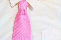 Roze stropdas die op wit overhemd wordt gebonden Stock Foto's