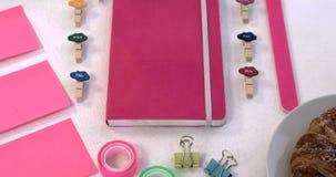 Roze toebehoren, croissant en kantoorbehoeftenpunten op witte achtergrond 4k stock footage