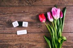 Roze Tulip Flowers en de datumscheurkalender op rustieke lijst voor 8 Maart, de Dag van Internationale Vrouwen, Verjaardag Royalty-vrije Stock Foto's