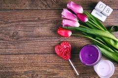 Roze Tulip Flowers, lolly, de datumscheurkalender en twee cendels op rustieke lijst voor 8 Maart, Internationale Vrouwen stock fotografie