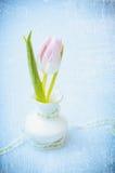 Roze tulp in vaas met lint op blauwe geweven achtergrond, romantische wijnoogst royalty-vrije stock fotografie