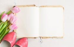Roze tulpen en leeg boek met vrouwen` s schoenen over witte houten Stock Fotografie