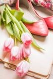 Roze tulpen en leeg boek met vrouwen` s schoenen over witte houten Royalty-vrije Stock Foto's