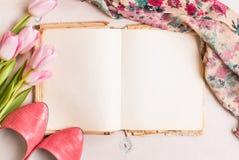 Roze tulpen en leeg boek met vrouwen` s schoenen over witte houten Stock Foto