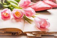 Roze tulpen en leeg boek met vrouwen` s schoenen over witte houten Stock Afbeelding
