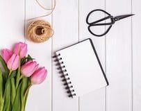 Roze tulpen en lege blocnote op de houten lijst, hoogste mening Stock Fotografie