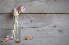 Roze tulpen in glasfles, op oude houten achtergrond met stock foto's