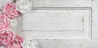 Roze uitstekende bloemen op oude deur Stock Afbeelding