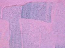 Roze verf op een muur met druppels en borsteltekens met de originele blauwe kleur die tonen onderaan stock foto's