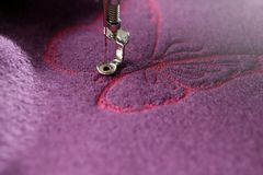 roze vlinder die op purpere gekookte wol worden gestikt stock foto