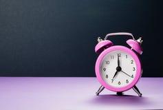 Roze wekker bij zeven uur in de ochtend op een purpere achtergrond stock afbeeldingen