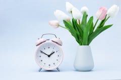 Roze wekker en een boeket van bloemen op een blauwe achtergrond royalty-vrije stock afbeelding