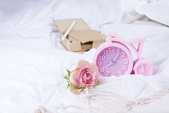 Roze wekker, wit bed en roze rozen Goedemorgen Uitstekende foto De ruimte van het exemplaar Royalty-vrije Stock Afbeelding