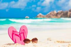 Roze wipschakelaars en zonnebril op een tropische overzeese toevluchtachtergrond Royalty-vrije Stock Foto