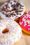 Roze, wit en bruin donuts op houten achtergrond wordt verglaasd die stock foto's