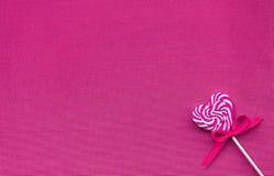 Roze zoete lolly in de vorm van een hart op een rode achtergrond royalty-vrije stock fotografie