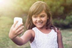 Roześmiana llittle dziewczyna robi selfie outdoors Zdjęcie Royalty Free